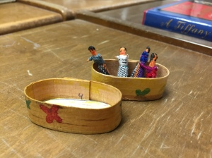 Very small dolls in a wooden pillbox.